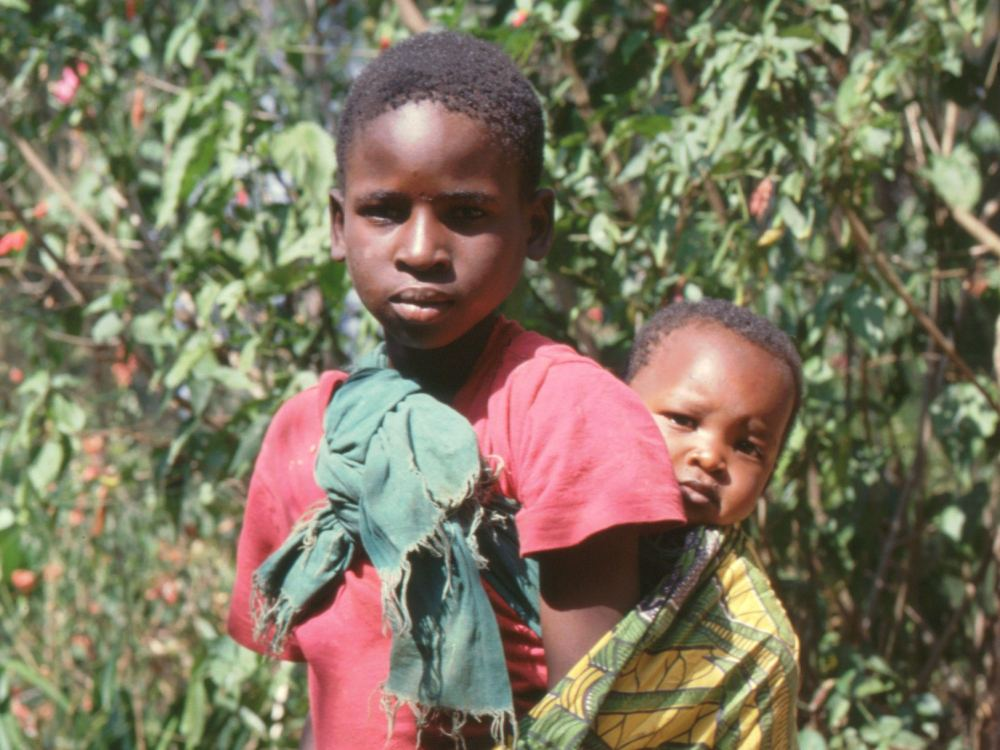 Pige med et lille barn på ryggen