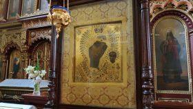 En Gudsmoderikon bag glas med lampe foran.