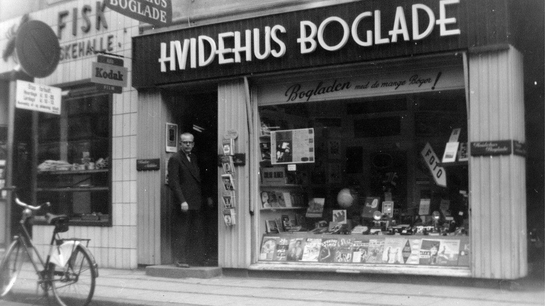 Hvidehus Boglade i Nørregade Vejle 1959. I døren står en af indehaverne, Kaj Jensen.